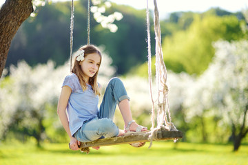 Cute little girl having fun on a swing in blossoming old apple tree garden outdoors on sunny spring day.