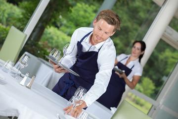waiter setting wedding table at restaurant