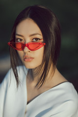 Asian woman fashion close-up portrait. Beautiful mixed race asian caucasian young girl perfect skin creartive art make-up wearing red sunglasses trendy white japanese kimono standing outdoors in