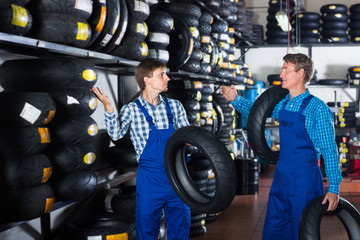 Two polite colleagues working with motorcycle tires