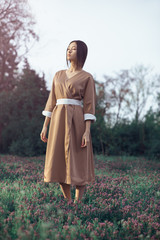 Asian woman wearing traditional japanese kimono outdoors in park. Stylish japanese model posing outdoors in fashionable dress. Young sensual girl standing on flower field in full length with closed
