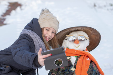 Adorable young girl is taking pictures of selfie with a snowman in beautiful winter park. Winter activities for children.