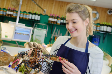 female working holding a lobster in a fish supermarket