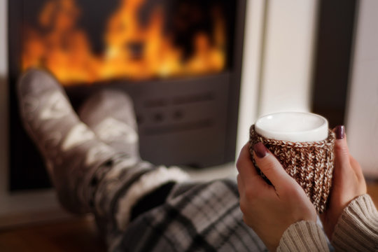 Girl drinking hot tea in front of the fireplace and warming legs on fire in long winter night. Woman is covered legs with blanket. Winter and cold weather concept. Close up, selective focus