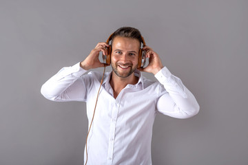 A smiling handsome young man in a white shirt listening to music on his headphones and standing in front of a grey background in the studio.