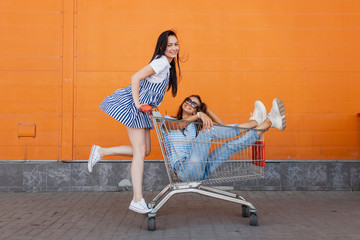 Two pretty slim dark-haired ladies,wearing casual outfit,have fun with a grocery cart near the shopping center.