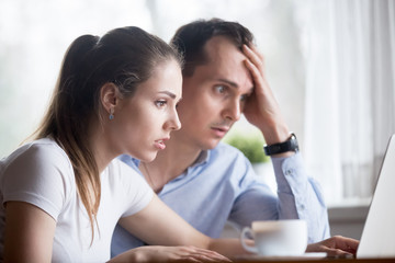 Head shot young millennial anxious spouses looking at computer screen. Married couple received bad news from bank about debt high taxes or forfeits. Verification password problems or data loss concept