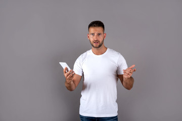 A worried handsome young man in a white tshirt using his smartphone and standing in front of a grey background in the studio.