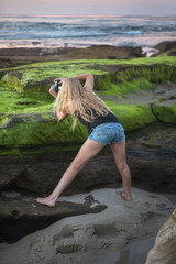blond girl with camera on seashore