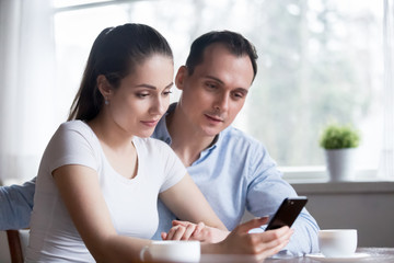 Millennial positive wife and husband sitting together in kitchen spend free time at home hold mobile phone reading email good news and messages. Spouses making order via internet online using gadget