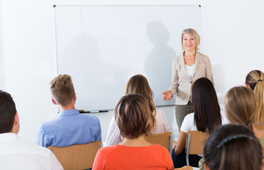 Mature female giving presentation for students