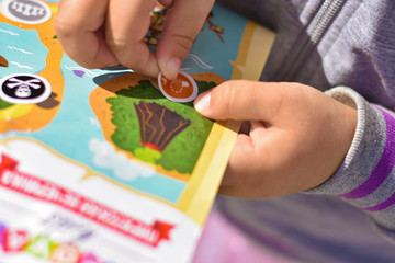 A child plays a pirate quest on a paper map, hands glue a sticker