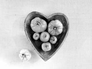 Black and white tomatoes in heart shaped bowl