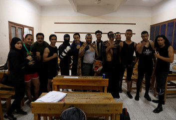 """Members of the Egyptian Arab Federation of Professional Wrestlers """"EWR"""" pose for a photograph at a class of the Abu Sultan High School, before a public fight in Ismailiya"""