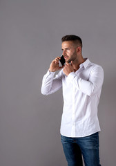 A serious handsome young man in a white shirt talking on his phone and standing in front of a grey background in the studio.