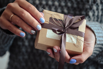 Gorgeous manicure, pastel tender color nail polish, closeup photo. Female hands hold a simple gifts over knit grey background