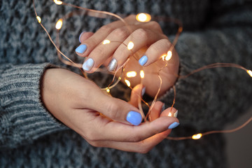 Gorgeous manicure, pastel tender color nail polish, closeup photo. Female hands hold a christmas...