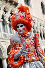 Carnival orange-silver mask and costume at the traditional festival in Venice, Italy