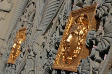 scultura di colore oro sul cancello del palazzo reale a torino