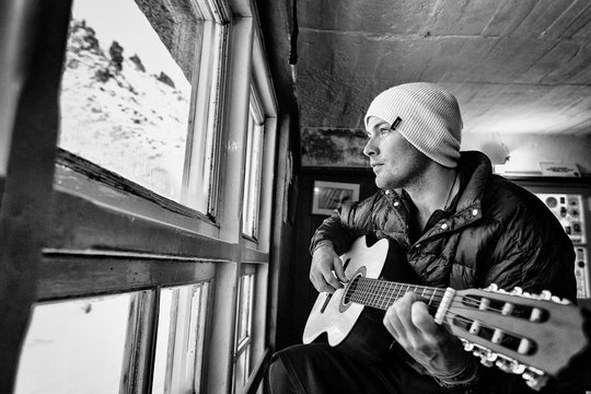 Man playing guitar by window