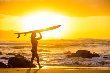 Woman with a surfboard walking along the beach