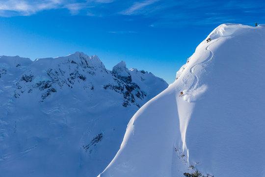 Skiers skiing a very steep mountain
