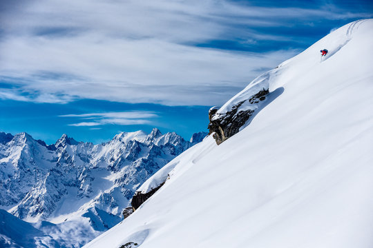 Skier skiing down a snowy steep mountain