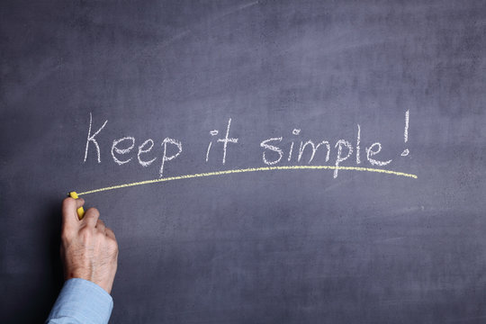 """A man's hand holding a piece of chalk and writing the phrase: """"Keep it simple!"""" on a blackboard"""