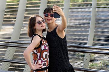 Asian women taking selfie near fence
