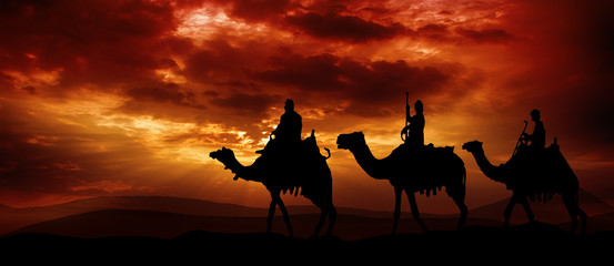 Three kings - traveling in the desert against the background of red clouds rising from the sun