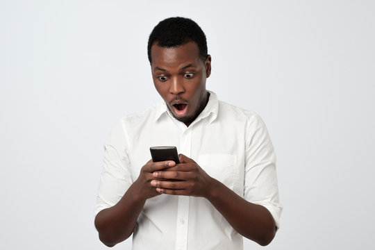 African man looking at phone seeing shocking news or photos with surprised emotion on his face