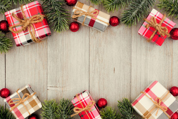Christmas double border of red and white patterned gifts and tree branches on a light gray wood background