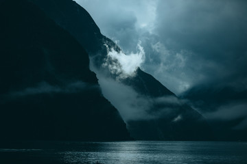 Mountains surrounded by water a fog