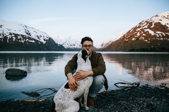 Man hugging his dog with a lake and snow capped mountains in the background