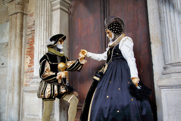 Carnival pair black-white-gold mask and costume at the traditional festival in Venice, Italy