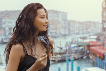 Woman with carnival mask in Venice. Attractive young sensual romantic woman standing on the pier against beautiful view on venetian chanal with boats and gondolas in Venice, Italy.