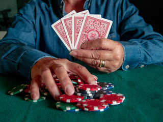 A person playing poker betting poker chips of various colors