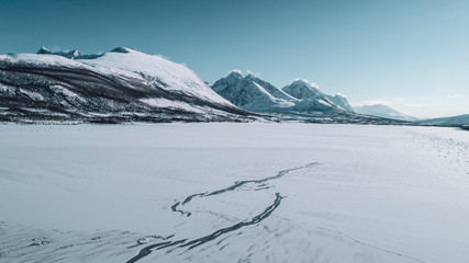A frozen body of water surrounded by snow capped mountains