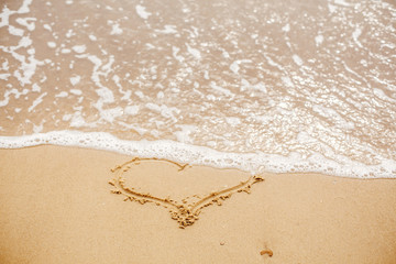 Heart written on sandy beach with wave near sea. Love concept. Happy valentine's day.  Honeymoon for newlyweds. Valentine day. Space for text. Happy holidays. Broken heart
