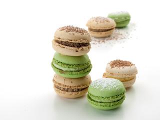 Varios macaroons de colores crema y verde con ralladuras de cololate sonbre un fondo blanco