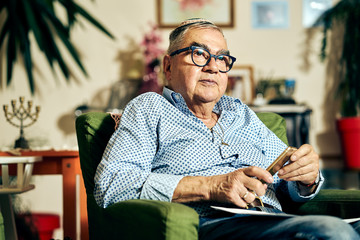 Jewish senior with glasses sitting in the armchair reading a torah book