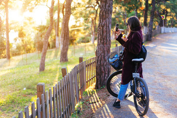 Beautiful young girl on a bicycle take a photos