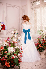 Beautiful girl model princess in the palace with flowers. Bride in a white dress. Woman in a luxurious vintage interior.