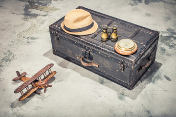 Vintage old classic travel trunk luggage with leather handles circa early 1900s, wooden toy plane, compass, binoculars, men's hat. Travel by air concept. Retro style filtered photo