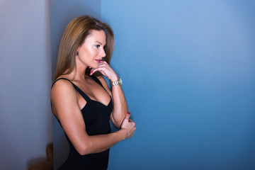 Sensual portrait of a beautiful woman in an elegant black dress while standing against a wall.