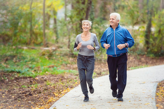 Smiling senior active couple jogging together in the park