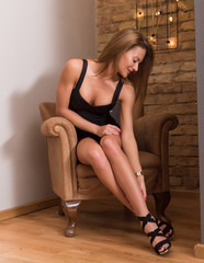 Sensual photo of a beautiful woman sitting on a chair and posing in an elegant black dress.