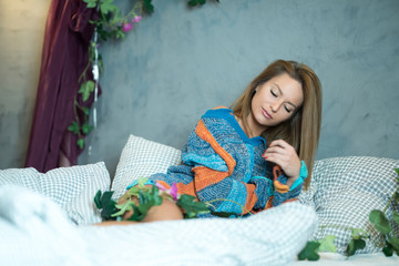 A beautiful woman lying on a bed in a modern apartment and wearing a colourful sweater.