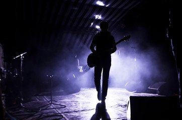 silhouette of a musician, a singer with a guitar on stage in the beams of searchlights. concept of music and rock festival - fototapety na wymiar
