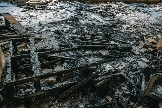 Remains of burnt wooden furniture on the floor of building after fire